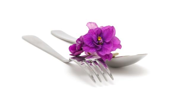 Colher e garfo com violetas em um fundo branco closeup