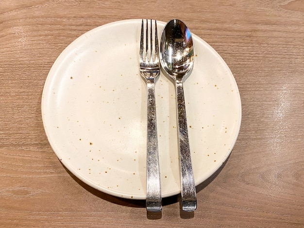 Colher e garfo de metal no prato de cerâmico em cima da mesa