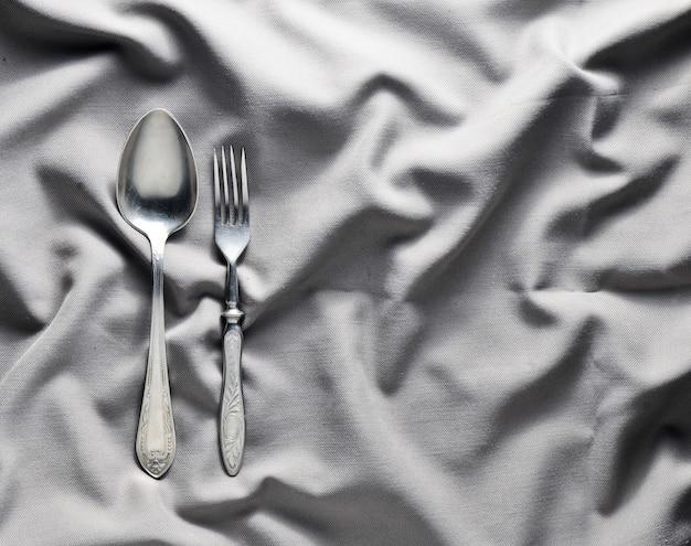 Colher e garfo em uma toalha de mesa de seda cinza. talheres vintage. copie o espaço. vista do topo.