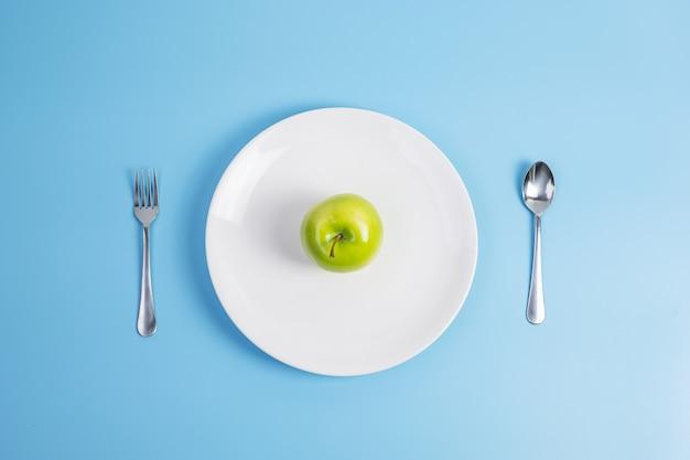 Colher e garfo, maçã verde no prato de cerâmica branca
