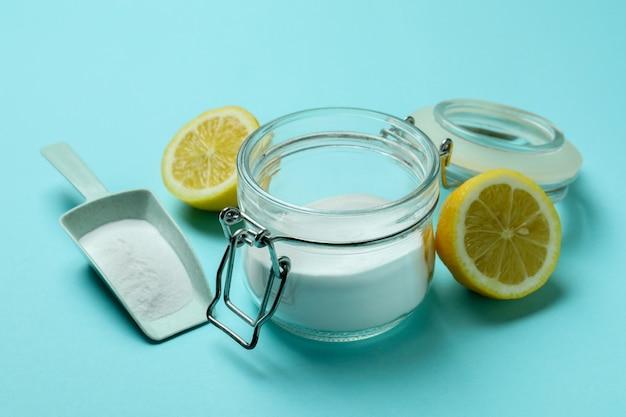 Colher e pote com pó de ácido e metades de limão no fundo azul isolado