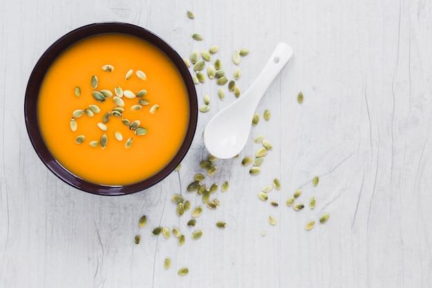 Colher e sementes perto da sopa de abóbora