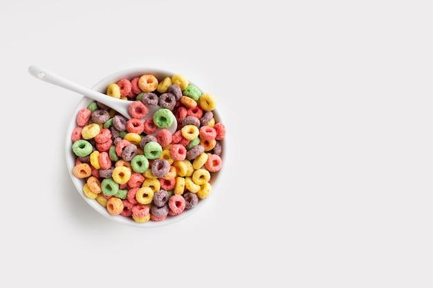 Colher e tigela de cereal colorido vista superior