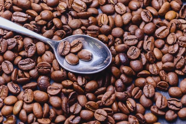 Colher em grãos de café sobre fundo preto de pedra