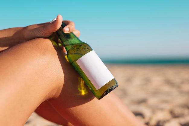 Colher mão feminina segurando cerveja na beira-mar