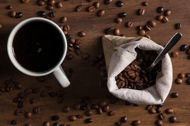 Colher no saco com grãos de café e copo de bebida