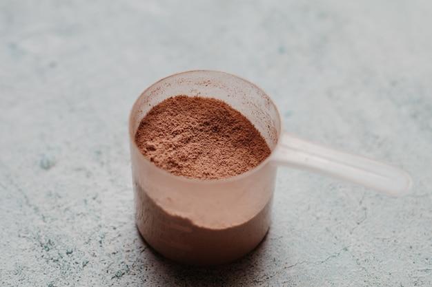 Colher ou colher de proteína de soro de leite com textura visível. sabor de chocolate. concreto