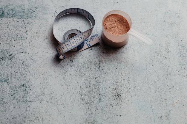 Colher ou colher de proteína de soro de leite com textura visível. sabor de chocolate. copie o espaço