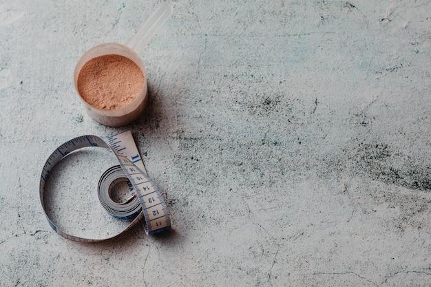 Colher ou colher de proteína de soro de leite com textura visível. sabor de chocolate. espaço da cópia