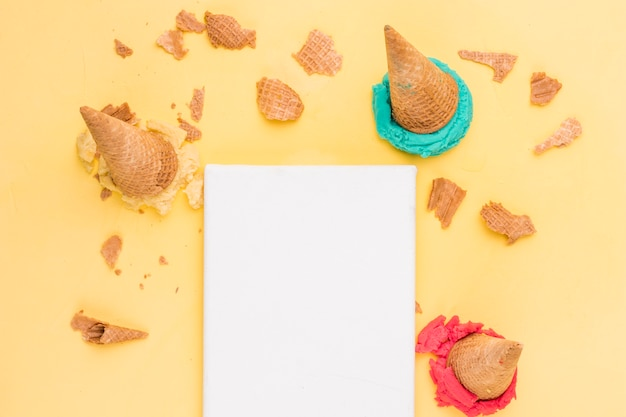 Colher para baixo waffles rachados do gelado brilhante e folha de papel vazia