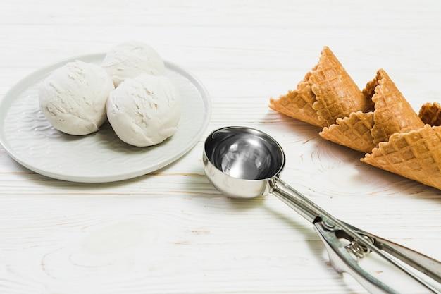 Colher perto de bolas de sorvete e cones de waffle
