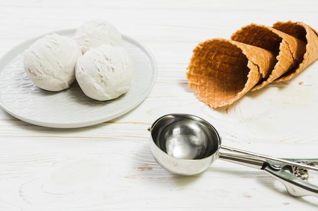 Colher perto de prato com sorvete e cones