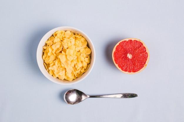 Colher; toranja cortada ao meio e flocos de milho em tigela branca sobre fundo branco