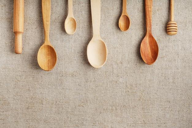 Colheres artesanais feitas de diferentes tipos de madeira ficam enfileiradas em um tecido de estopa de maconha. vista superior, espaço livre