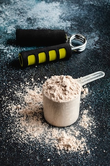 Colheres cheias de proteína em pó para nutrição fitness para iniciar o treinamento