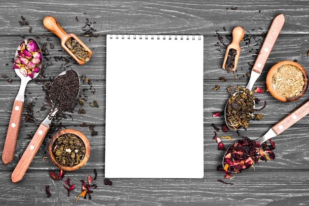 Colheres com chá de ervas e caderno