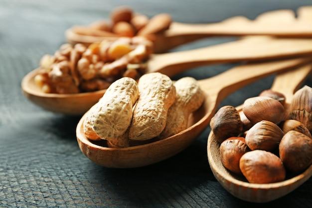 Colheres com nozes, pistache, amêndoas, bolotas e amendoim, em madeira cinza