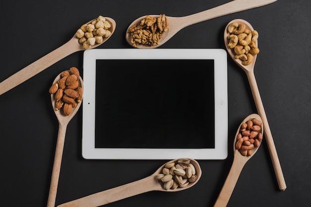 Colheres com nozes sortidas em torno de tablet
