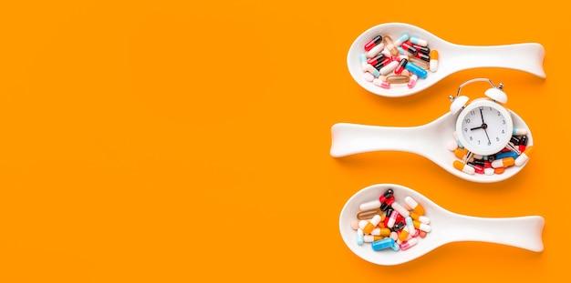 Colheres com pílulas com cópia-espaço