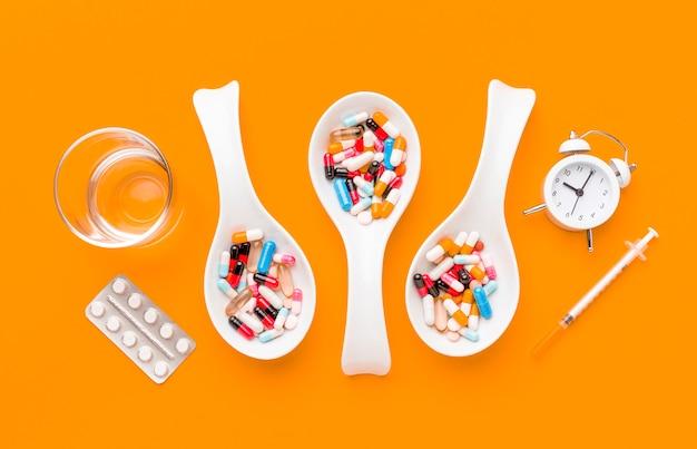 Colheres com pílulas e relógio