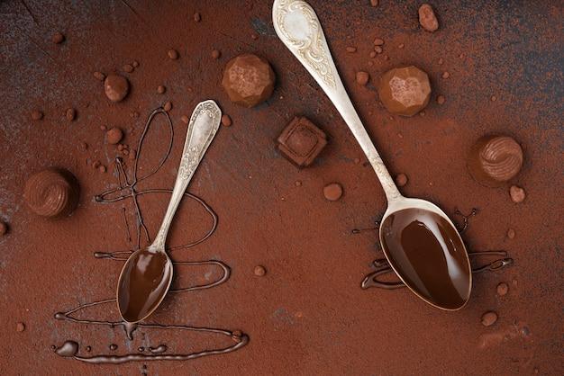 Colheres com trufas de calda de chocolate e cacau em pó