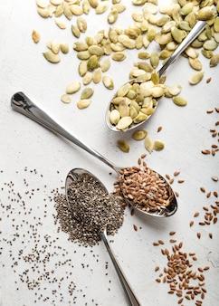 Colheres de alta vista cheias de várias sementes