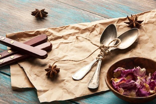 Colheres de chá vintage e pétalas de rosa sobre fundo azul de madeira