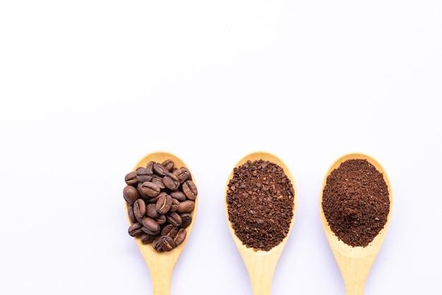 Colheres de madeira cheia de grãos de café e café moído esmagado no fundo branco