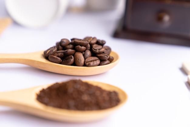 Colheres de madeira cheias de café moído esmagado sobre fundo branco, close-up