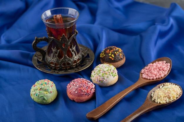 Colheres de madeira cheias de granulado colorido com uma xícara de chá.
