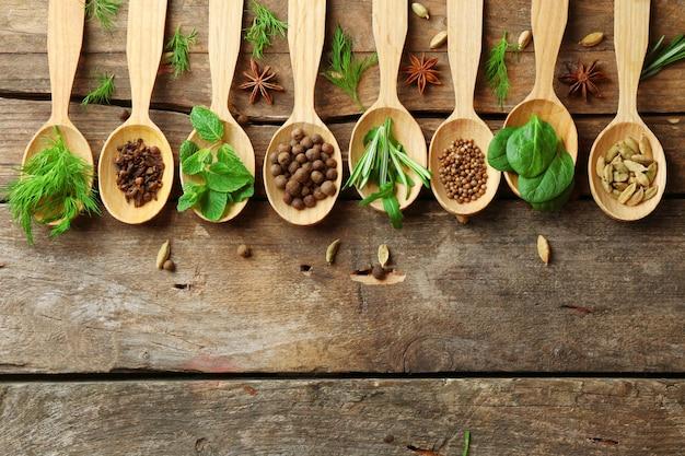 Colheres de madeira com ervas frescas e especiarias no fundo da mesa de madeira