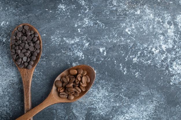 Colheres de madeira com gotas de chocolate e grãos de café.