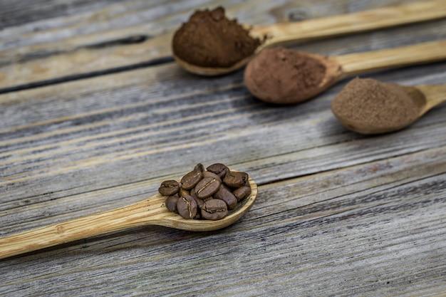 Colheres de madeira com grãos de café e pó de café