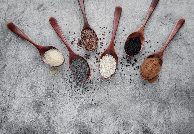 Colheres de madeira com várias sementes saudáveis e especiarias em fundo cinza de concreto