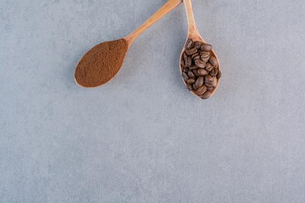 Colheres de madeira de grãos de café torrados e moídos em fundo de pedra.