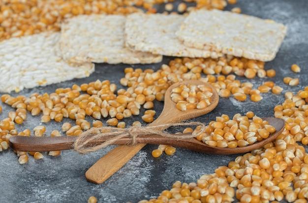 Colheres de madeira de grãos doces com pão de arroz crocante.