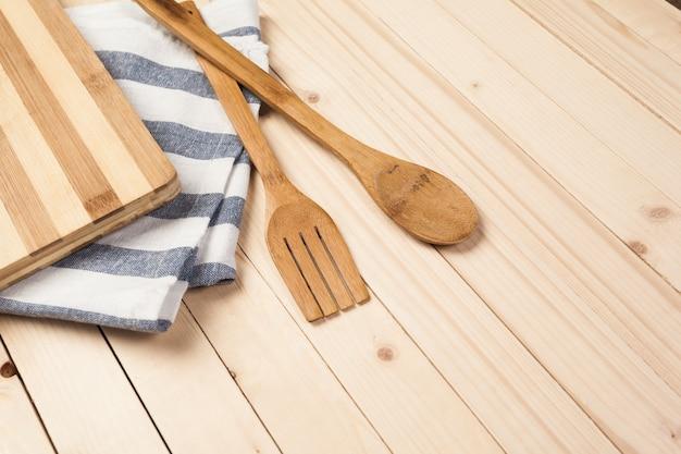 Colheres de madeira e outras ferramentas de cozimento com guardanapos azuis na mesa de cozinha.
