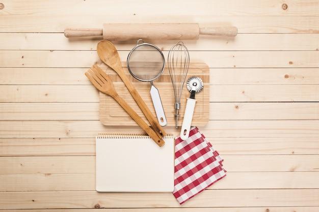 Colheres de madeira e outras ferramentas de cozimento com guardanapos vermelhos na mesa de cozinha.