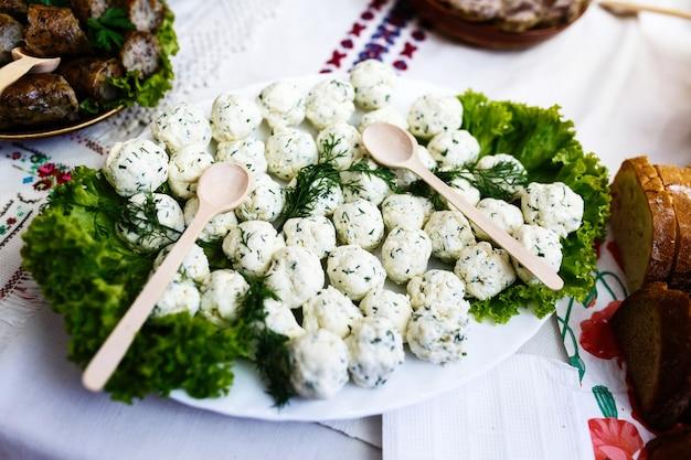 Colheres de madeira estão no prato com bolas de queijo e vegetação