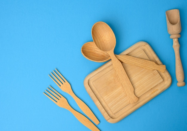 Colheres de madeira, garfos e tábua de corte retangular, vista superior