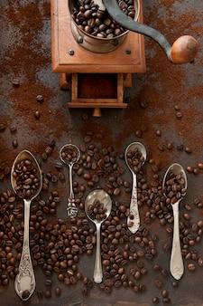 Colheres de metal com grãos de café de aroma e moedor de café em fundo escuro