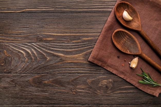 Colheres de pau, alho e alecrim em fundo de madeira