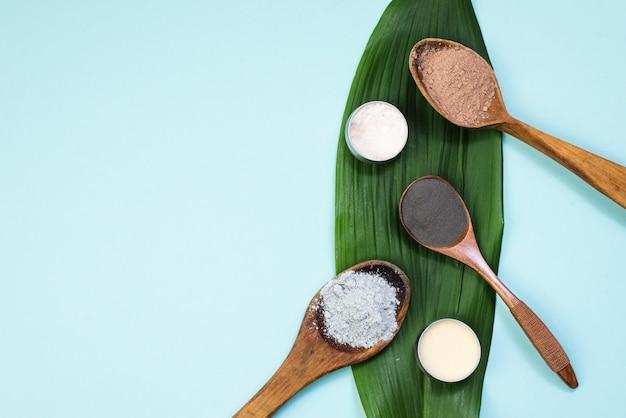 Colheres de pau com argila preta, vermelha, laranja e cinza em uma folha de palmeira verde. creme, bálsamo e pó para criar cosméticos a partir de ingredientes naturais. copyspace, plana leigos