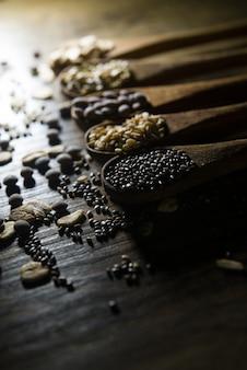 Colheres de pau com cereais e sementes de madeira