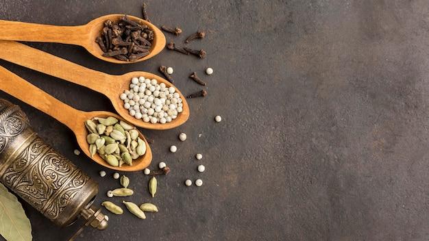 Colheres de pau com sementes e cópia-espaço