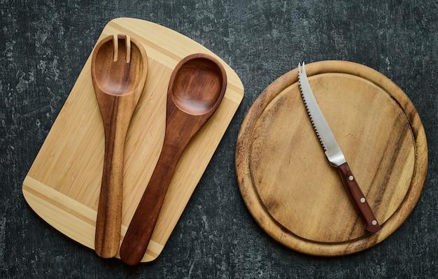 Colheres de pau e faca de tomate em tábuas de corte, vista superior