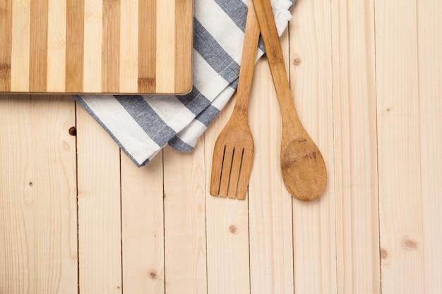 Colheres de pau e outras ferramentas de cozinha com guardanapos azuis na mesa da cozinha.