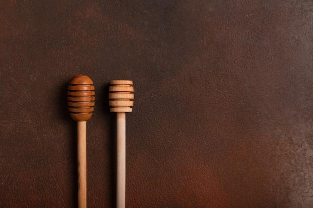 Colheres de pau para mel em uma mesa escura
