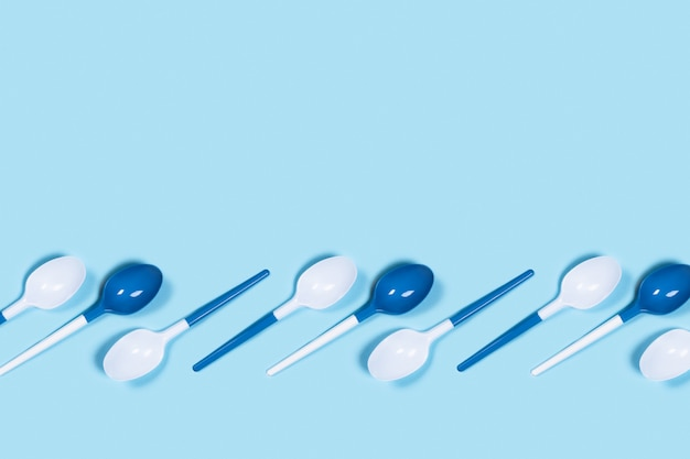 Colheres de plástico na mesa azul.