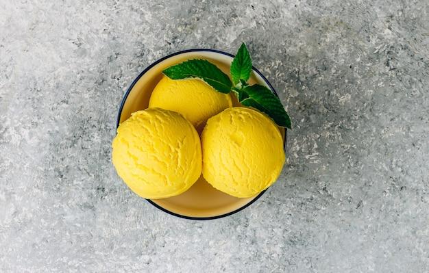 Colheres de sorvete de limão em uma tigela sobre fundo de pedra